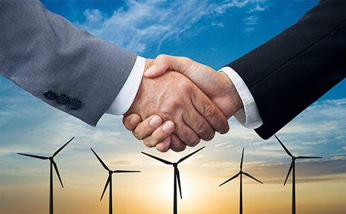 Business men shaking hands in front of windmill background