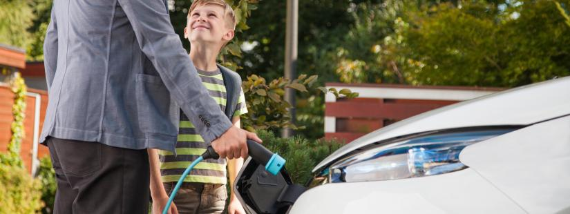 Father and Son charging electric vehicle